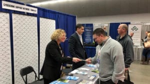 Volunteers distribute pamphlets at the Comcast and Cybercrime Support Network booth.