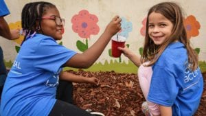 Two young Comcast Cares Day volunteers paint a mural.