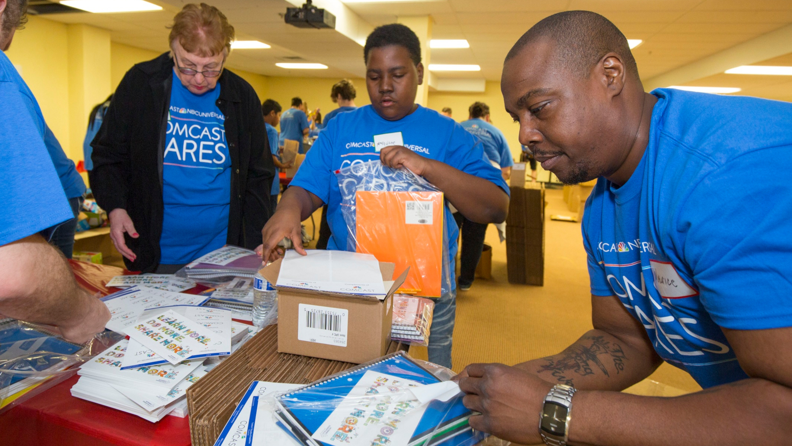 Comcast Cares Day volunteers pack homework kits for young students.