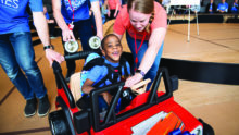 Easterseals volunteers help a young boy drive a toy car.
