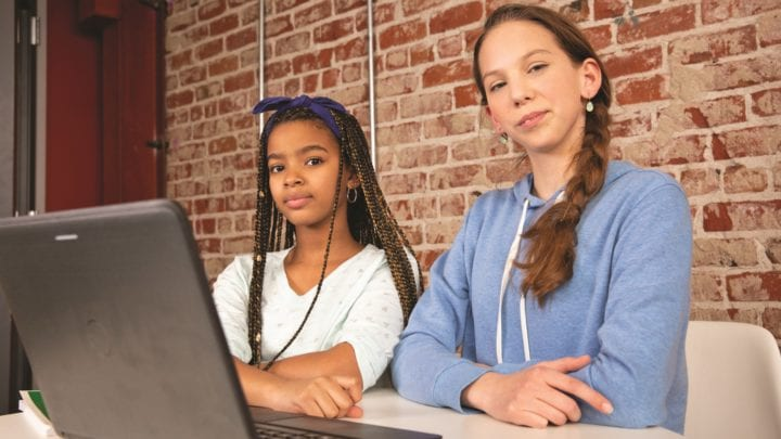 Two young teens at desk with laptop